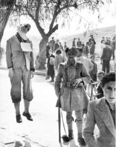 Ιλίσια, Απρίλης του '44. Ταγματασφαλίτης ποζάρει δίπλα σε απαγχονισμένο νεολαίο της ΕΠΟΝ